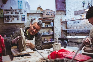 Concentrated male craftsperson working at table