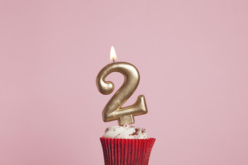Number 2 gold candle in a cupcake against a pastel pink background