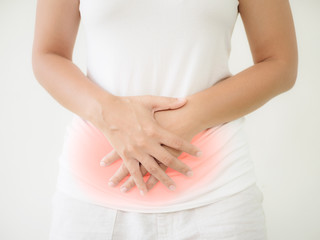 Woman having a stomachache, or menstruation pain with white background. Health care and medical concept.