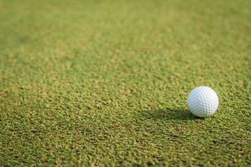 Golf ball on green grass course lawn field park nature background with empty copy space