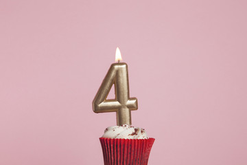 Number 4 gold candle in a cupcake against a pastel pink background