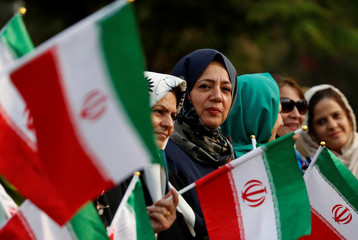 People hold Iranian flags as they wait for the arrival of President Hassan Rouhani at Begumpet Airport in Hyderabad