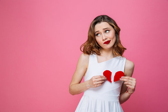 Confused woman holding broken heart. Looking aside.