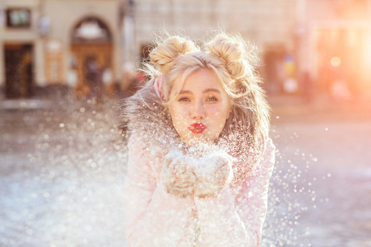 Happy woman blowing snow outdoors in sunny winter city. Girl having fun in the street.