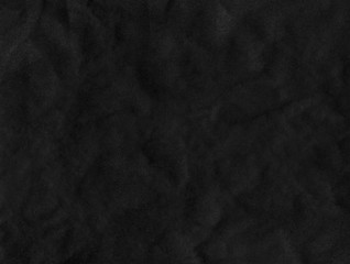 Black wrinkled paper texture. Dark textured surface background
