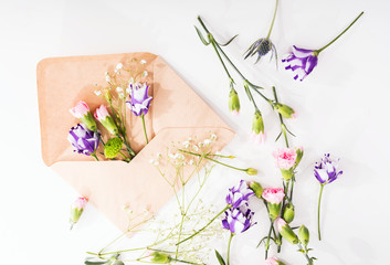 Opened envelope with flowers arrangements isolated on white background, top view. Festive greeting concept. Artist workplace. Close up photo. Macro