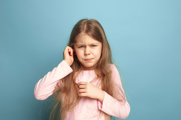 The Ear ache. Teen girl on a blue background. Facial expressions and people emotions concept