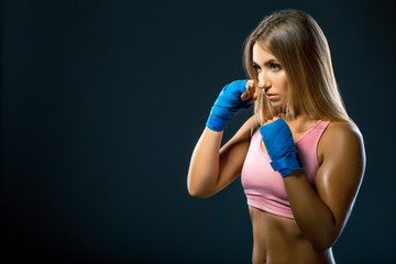 fitness woman with the blue boxing bandages, studio shot. Space for text. athlete preparing for a shock in training