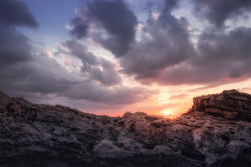 Sundown with clouds and rocks