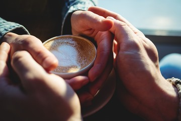 Close-up of man and woman holding coffee cup at cafeteria