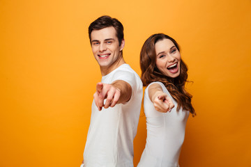 Portrait of a joyful young couple pointing fingers Wall mural