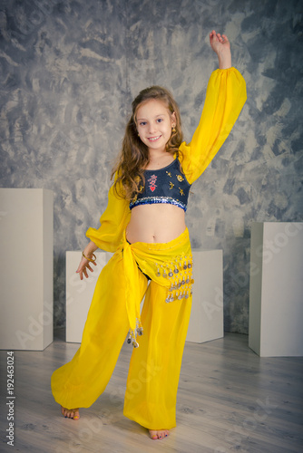 81ac837460823 dancer girl. Girl, closing with a yellow Indian handkerchief. Eastern dance.  Portrait of a smiling girl dancer in studio. Dancing teenage girl in a ...