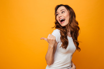 Laughing brunette woman in t-shirt looking and pointing away Wall mural