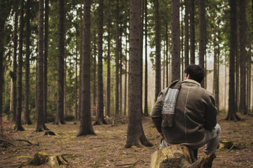 Man sitting in the forest alone in nostalgic atmosphere