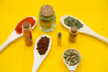 Glass bottles and spoons with dry spices and fresh herbs on a wooden cutting board with yellow background, top view, close up