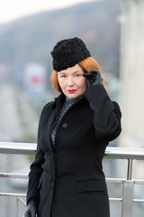Styled woman in black coat. Rude lady in coat, hat and gloves. Woman's serious look at you. Lady coquettishly meet guy. Aged woman hide her embarrassment