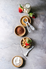 Ingredients for cooking chocolate mug cakes. Flour, cocoa powder, sugar, caramel in wooden bowls, milk, strawberries and mint served with spoons over grey texture background. Top view, space