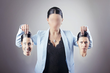 Young business woman choosing her identity for a blank face, holding a happy face and a sad face, can't decide between the two
