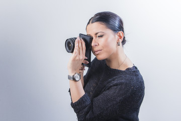 Young witty woman focusing her cell phone camera with a changeable lens