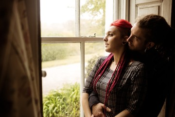 Romantic couple embracing while looking through window