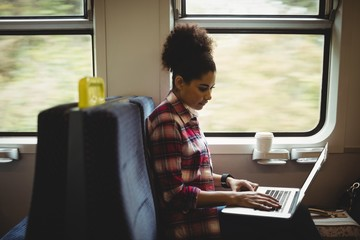 Young woman using laptop in train