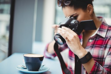 Woman photographing coffee cup at restaurant