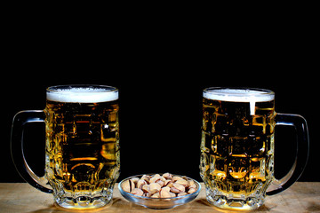 Two beer mugs and pistachios against black background
