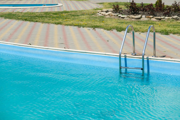 Swimming pool with metal stairs outdoor in a private house.
