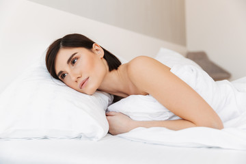 Portrait of a pretty young woman lying in bed