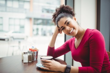 Portrait of cheerful woman with coffee at restaurant