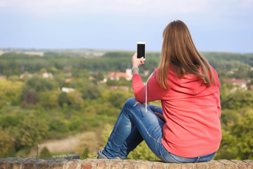 Girl sitting on a wall facing her back and make picture with her smartphone.