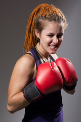 Young woman boxer with dreadlocks with clenched teeth