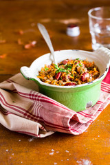 White cabbage stew with green lentil and sausages in a pot on a wooden table, selective focus