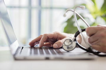 Doctor entering patient notes on laptop in surgery