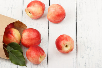 Ripe red peaches in the paper bag on the white wooden table