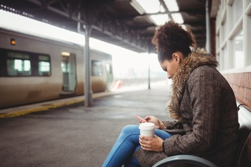 Woman using phone at railway station