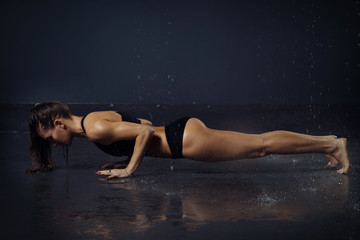 beautiful young girl in top and shorts doing yoga pose under the drops of water