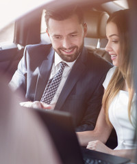 Smiling business people working in backseat of car