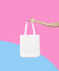 hand holding bag canvas fabric for mockup blank template isolated on color background.