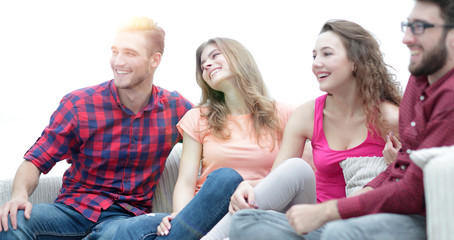 group of cheerful friends sitting on the couch
