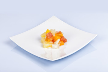 Tropical fruit salad dessert in oriental dish and isolated on white