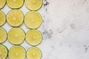 Lime slices in rows on a light background copy space