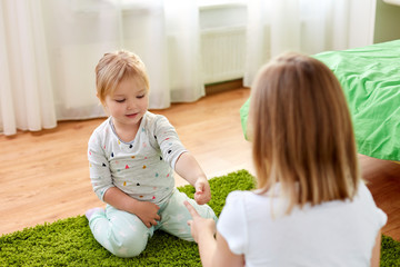 girls playing rock-paper-scissors game at home
