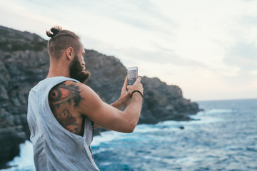 young man bearded standing cliff taking picture