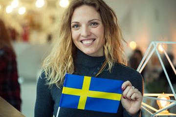 Woman holding a flag of Sweden.