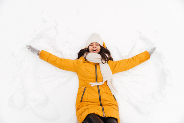 Happy playful lady lying on snow and making snow angel figure