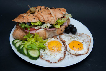 White Plate with Fried Eggs and Croissant with Fresh Vegetables over Black Background.