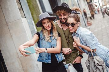 Friends having fun while taking selfie on a sidewalk