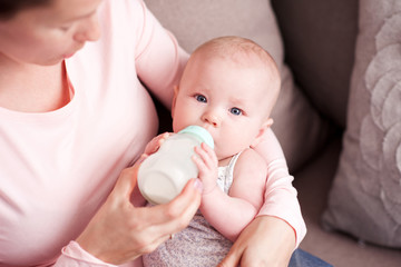 Mother feeding baby in room. Infant holding drinking milk from bottle closeup. Looking at camera. Healthy nutrition.