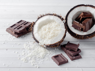 Fresh organic coconut broken into two parts with chocolate on a rustic wooden background